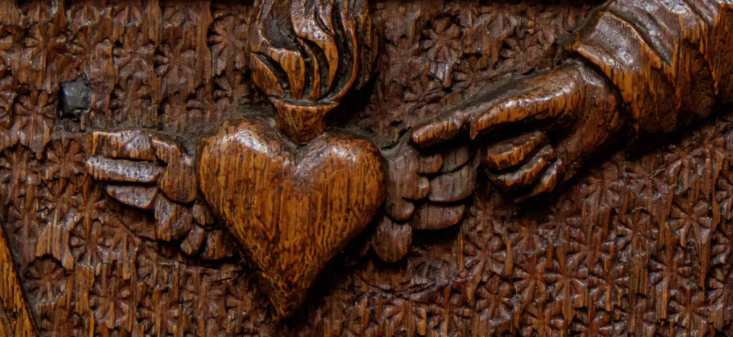 Herz Jesu Schnitzerei an Kirchenbank